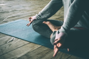 women who is learning the health benefits of yoga while at home
