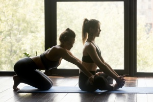 a yoga teacher and student working on practice