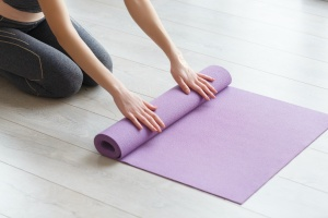 women rolling up mat after Savasana