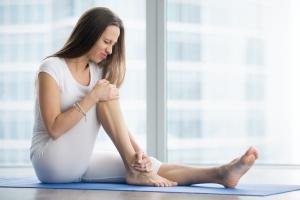 women holding her yoga injuries