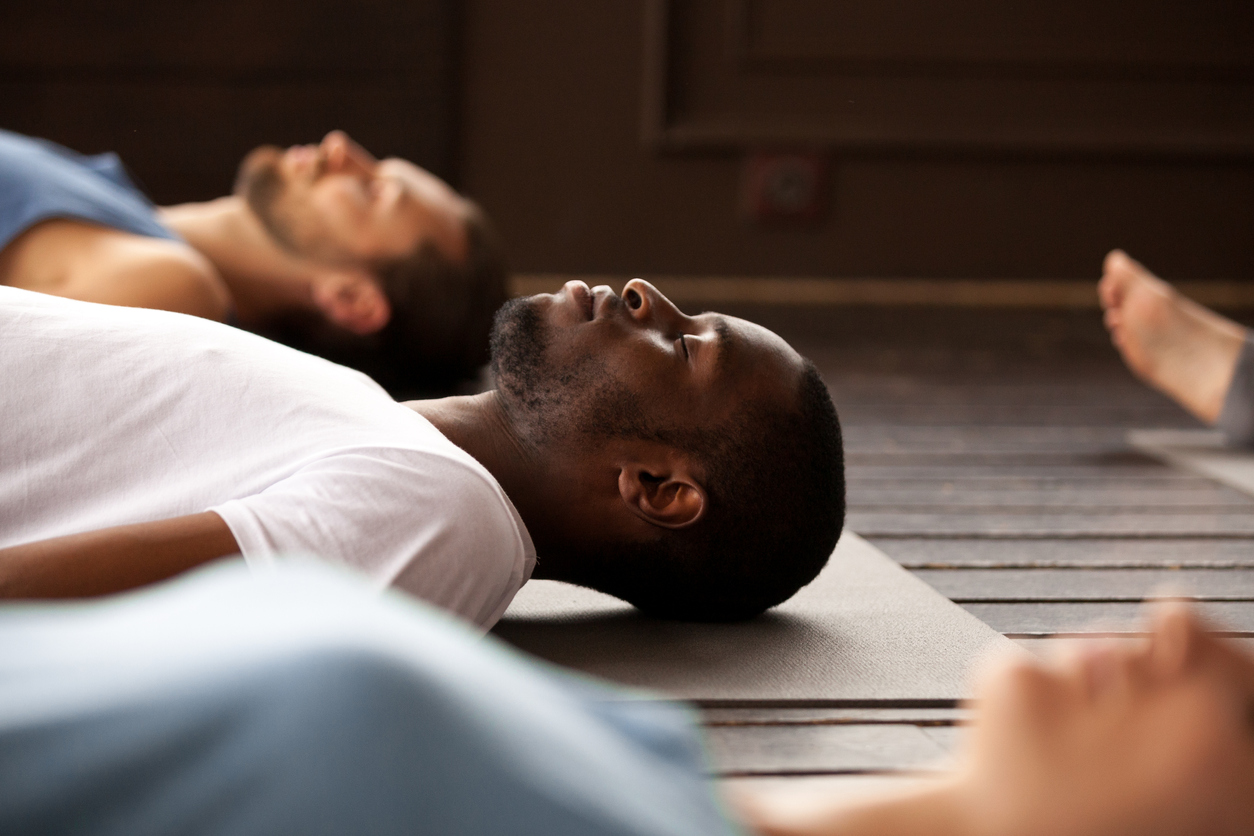 Group of sporty people in Savasana exercise