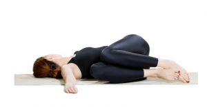 demonstration of yoga pose on women laying on the ground