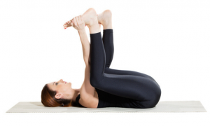 women showing how a pose while grabbing her feet with her hands