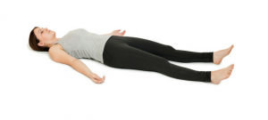 women laying on the ground not moving in yoga pose