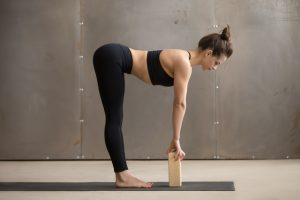 women using wooden block as help with her yoga practice pose