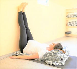 women practicing with her legs up against the wall and blanket under her in order to stretch
