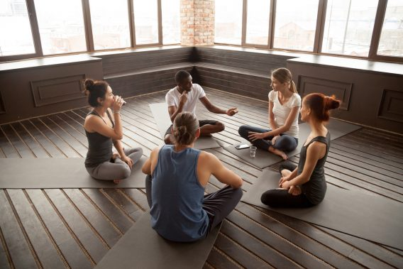 African-american yoga instructor talking to diverse group sitting on mat