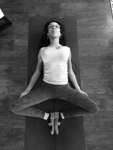 black and white on women laying on ground on her yoga mat stretching