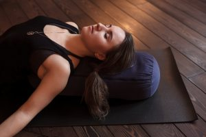 women laying on ground with pillow doing yoga poses