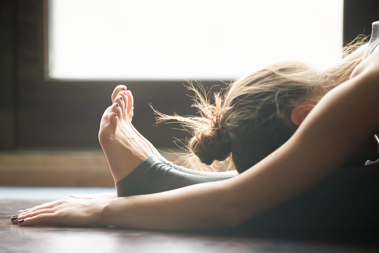 Young woman in paschimottanasana pose, home interior background,