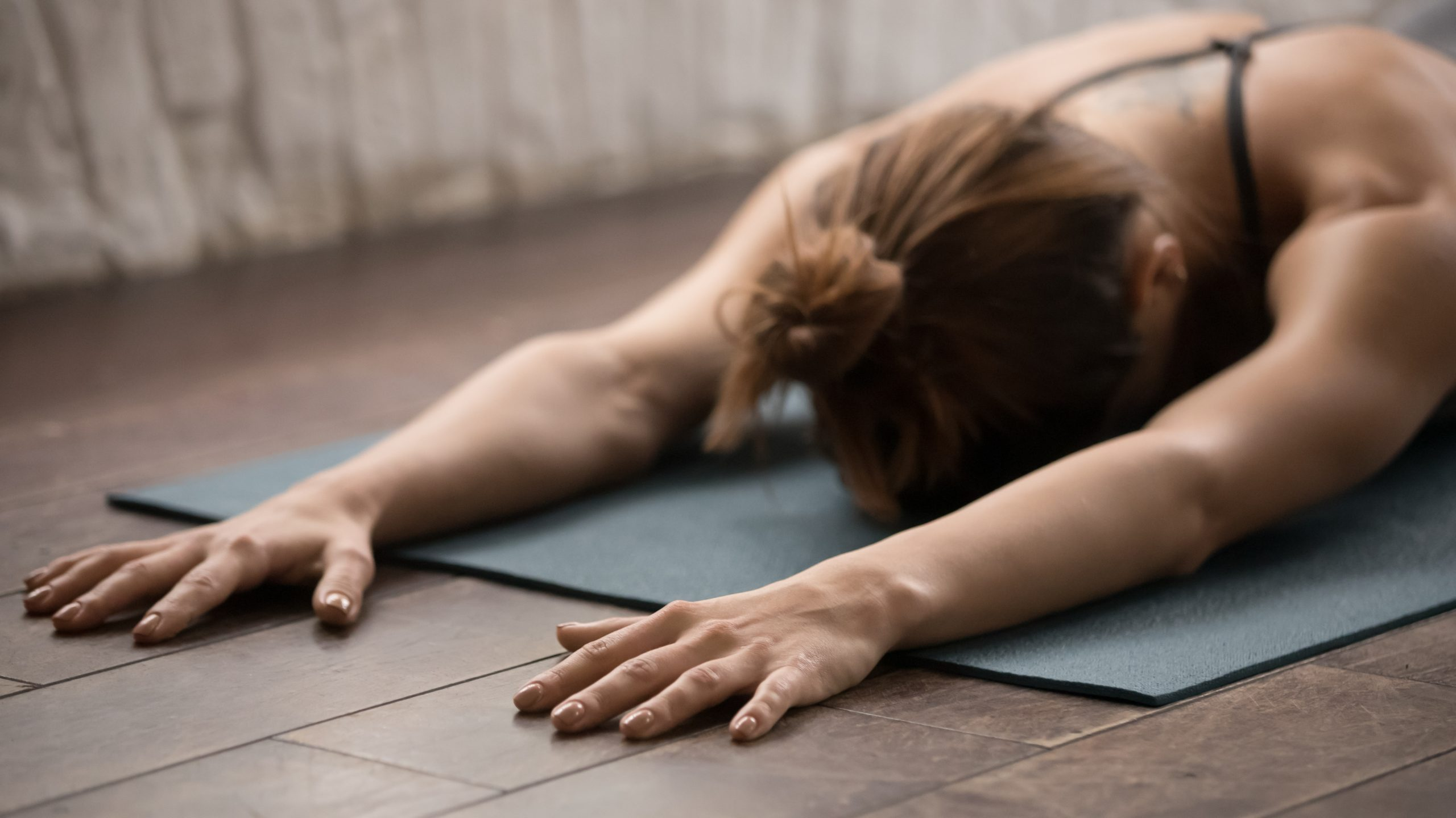 Attractive woman practicing yoga, relaxing after training, lying face down