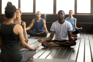 Group of young people learning from a new yoga teachers