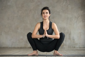 Young sporty woman practicing yoga, doing Garland exercise, Malasana pose, working out, wearing sportswear, black pants and top, indoor full length, gray wall in yoga studio