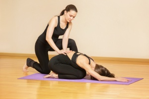 new yoga teachers is helping young woman to make asana pose at gym.