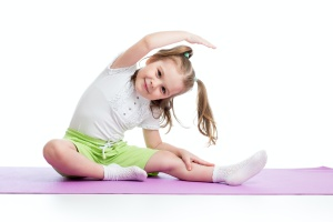 little girl learning from someone who has learned teaching children yoga