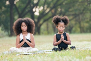 two girls taking a lesson from someone teaching children yoga